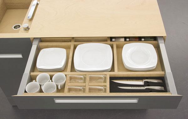 Дизайн кухни. Под разделочной доской столешницей -- удобные ящик с отделениями для посуды