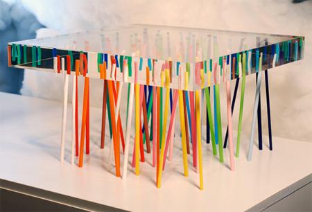Небольшой столик с толстой прозрачной столешницей и разноцветными ножками.