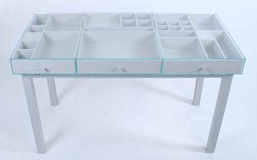 Стол, в котором всё содержимое ящиков видно сквозь стеклянную столешницу
