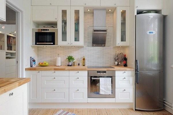 Белая кухня с холодильником цвета металлик