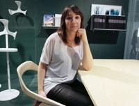 Дизайнер по мебели Моника сидит на стуле собственного дизайна.