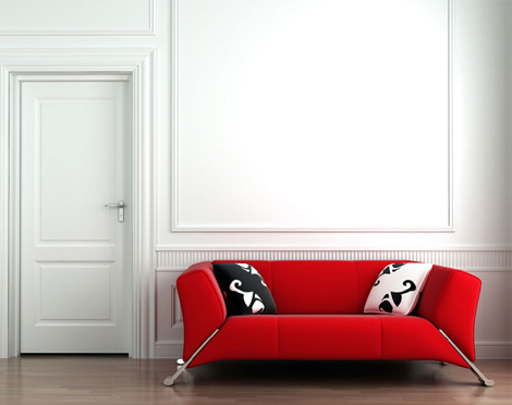 Интерьер гостиной. Красный диван с ещё белой плиткой на стене.
