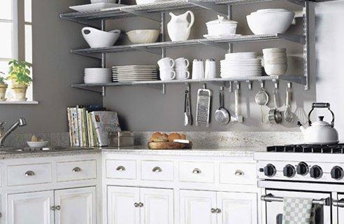 Белая посуда на сером фоне стен. Открытые полки.