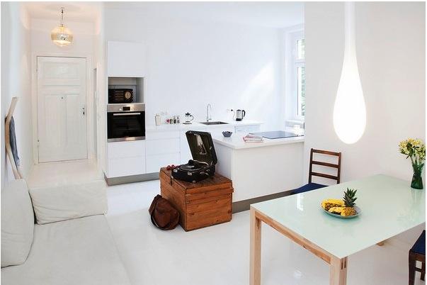 Открытая белая кухня в маленькой квартире